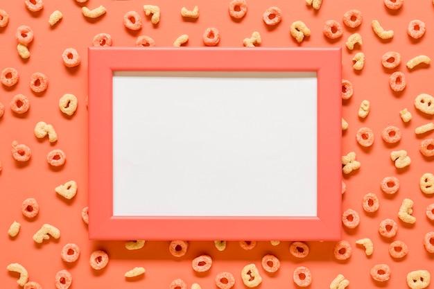 Maqueta en blanco marco y cereales de desayuno en superficie coloreada