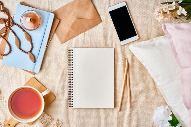 Maqueta con bloc de notas en cama y accesorios para mujer, té, galletas, almohadas, flores.