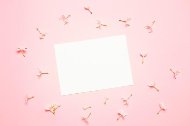 Maqueta de boda con lista de papel blanco y flores sobre fondo azul