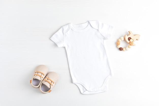 Maqueta de body infantil blanco hecho de algodón orgánico con accesorios ecológicos para bebés. plantilla de mono para marca, logotipo, publicidad. endecha plana, vista superior