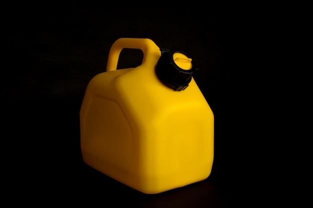 Maqueta de un bote de plástico amarillo para combustible de automóvil sobre un fondo negro. recipiente para líquidos y combustibles peligrosos.
