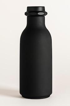 Maqueta de botella de agua negra sobre un fondo blanco roto