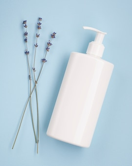 Maqueta de botella de crema de manos junto a lavanda