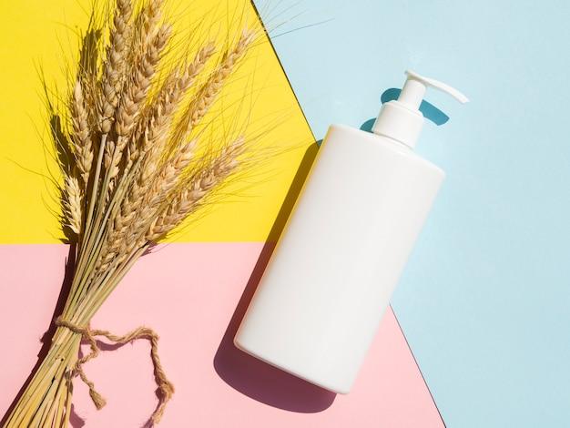 Maqueta de botella de loción de primer plano junto al brunch de trigo