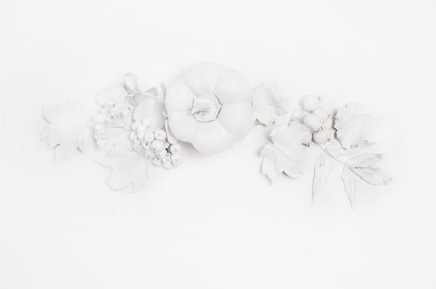 Maqueta de calabaza blanca, bayas y hojas sobre una madera