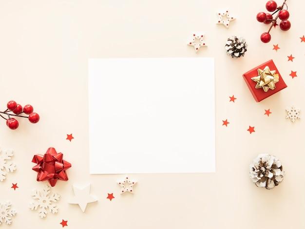 Maqueta de carta de navidad con tarjeta postal en blanco y adornos navideños sobre fondo blanco.
