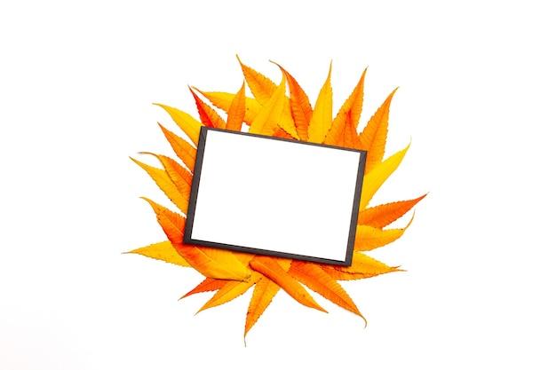 Maqueta de carta vacía en blanco o postal con sobre negro sobre hojas amarillas y rojas otoñales