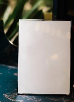 Maqueta de cartel a4 blanca dentro de un soporte de acrílico