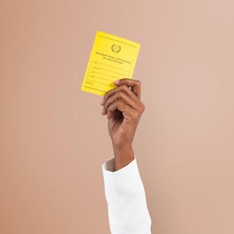 Maqueta de certificado de vacuna covid-19 psd sostenido por la mano de un empresario