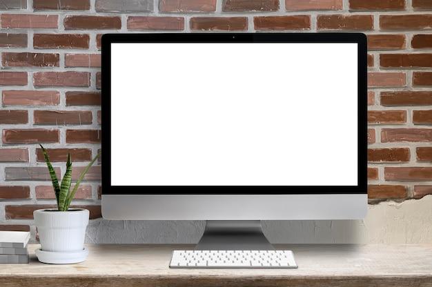 Maqueta computadora de escritorio blanco pantalla en blanco, planta de interior y libro sobre mesa de madera, pantalla en blanco para diseño gráfico.