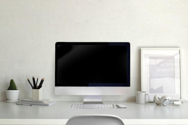 Maqueta de computadora de escritorio con marco de póster vacío y suministros de oficina en la mesa de trabajo