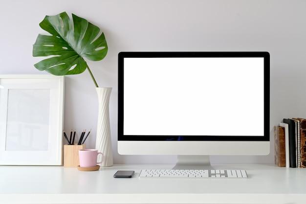 Maqueta de la computadora de escritorio de pantalla en blanco en la mesa. espacio de trabajo en el estudio de casa