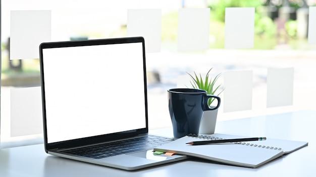 Maqueta de computadora portátil con cuaderno, lápiz y café en la mesa de la oficina moderna