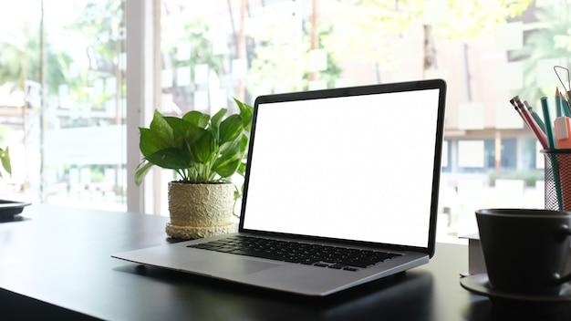 Maqueta de computadora portátil con pantalla en blanco en escritorio negro y suministros de oficina. para montaje de exhibición de productos.