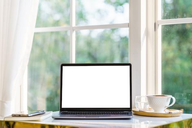 Maqueta de computadora portátil con pantalla vacía con cuaderno, taza de café y teléfono inteligente en el lado de la mesa de la ventana de la cafetería en la cafetería, pantalla blanca