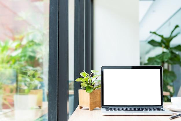 Maqueta de computadora portátil con pantalla vacía con taza de café en la mesa de la cafetería