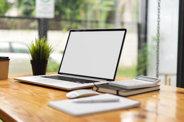 Maqueta de computadora portátil con papelería, ratón portátil y calculadora en la mesa de madera en el café