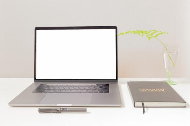 Maqueta de la computadora portátil y la pluma con el cuaderno sobre la mesa blanca.