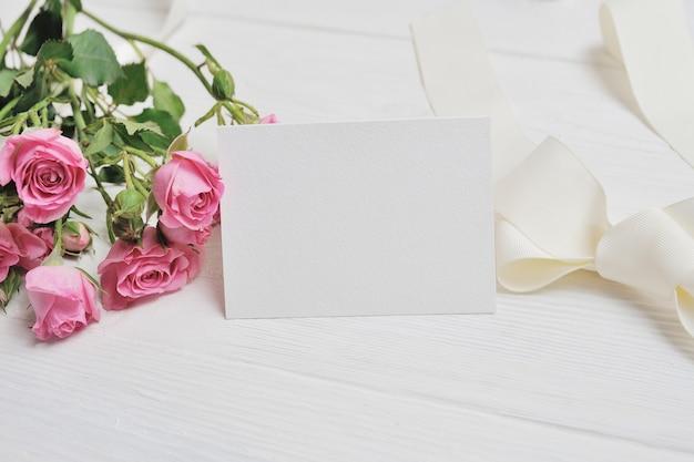 Maqueta corazones de origami blanco de papel con rosas rosadas. tarjeta de citas de san valentín