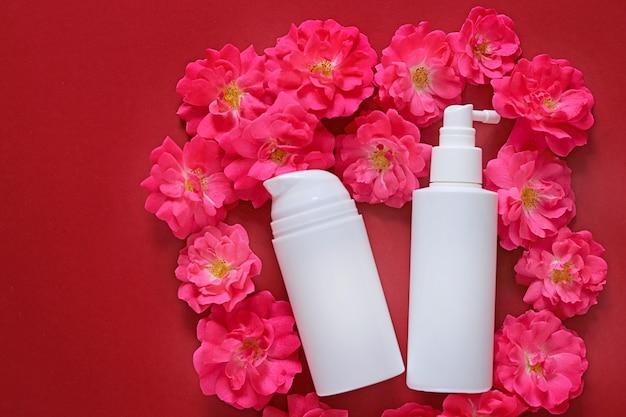 Maqueta de cosméticos y cuidado de la piel. crema y suero con extracto de rosa en frascos cosméticos blancos sobre rosas rosadas