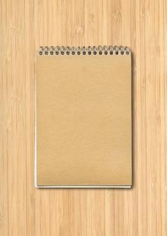 Maqueta de cuaderno cerrado en espiral, cubierta de papel marrón, aislado sobre fondo de madera