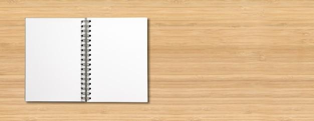 Maqueta de cuaderno espiral abierto en blanco aislado en banner horizontal de madera