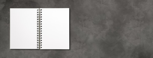 Maqueta de cuaderno espiral abierto en blanco aislado en banner de hormigón oscuro