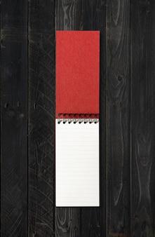 Maqueta de cuaderno espiral abierto en blanco aislado sobre fondo de madera negra