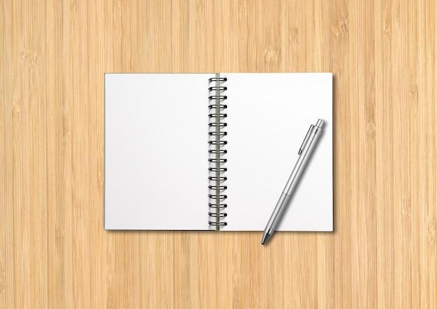 Maqueta de cuaderno espiral abierto en blanco y bolígrafo aislado sobre fondo de madera