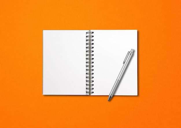 Maqueta de cuaderno espiral abierto en blanco y bolígrafo aislado sobre fondo naranja
