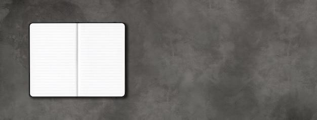 Maqueta de cuaderno forrado abierto negro aislado sobre fondo de hormigón oscuro. banner horizontal