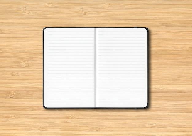 Maqueta de cuaderno forrado abierto negro aislado sobre fondo de madera
