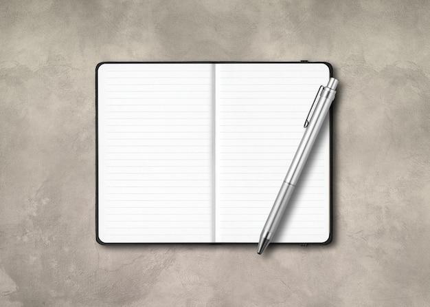 Maqueta de cuaderno forrado abierto negro con un bolígrafo aislado sobre fondo de hormigón