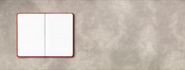 Maqueta de cuaderno forrado abierto rojo aislado sobre fondo de hormigón. banner horizontal