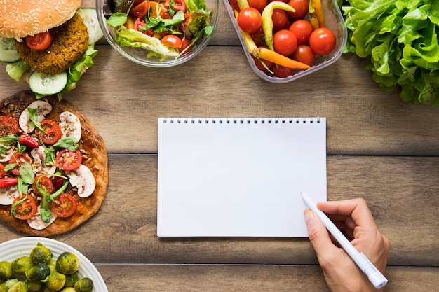 Maqueta de cuaderno junto a deliciosos platos veganos