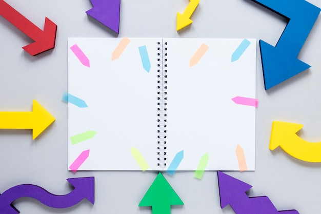 Maqueta de cuaderno plano con flechas coloridas