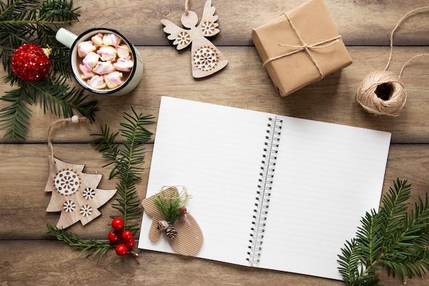 Maqueta de cuaderno rodeada de adornos navideños