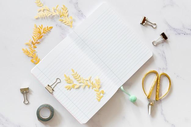 Maqueta de cuaderno con vista superior de tijera