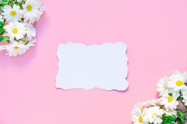 Maqueta de cumpleaños o boda con flores de crisantemos blancos y lista de papel blanco vacío sobre fondo rosa pastel