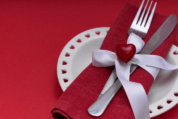 Maqueta del día de san valentín. plato blanco en forma de corazón y cubiertos de plata.