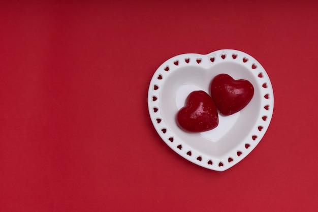 Maqueta del día de san valentín. plato blanco en forma de corazón.