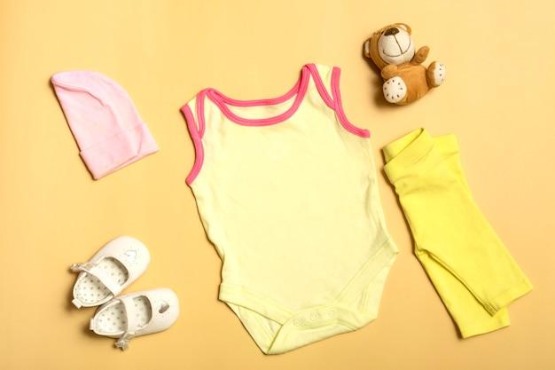 Maqueta para diseño y colocación de logotipos, publicidad. body de bebé beige, vista superior, maqueta sobre un fondo amarillo.