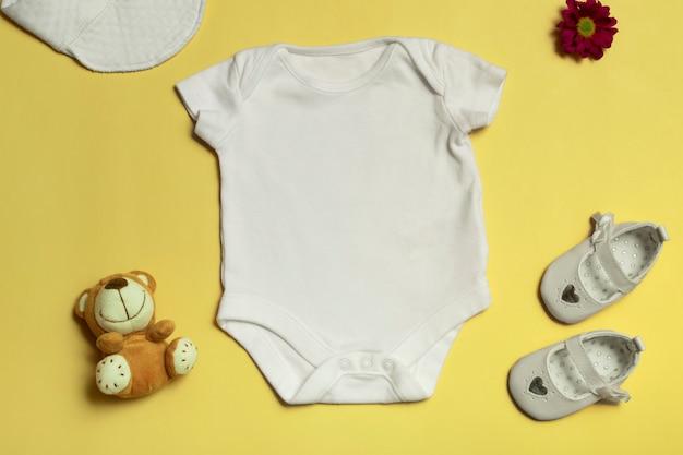 Maqueta para diseño y colocación de logotipos, publicidad. body de bebé blanco, vista superior, maqueta sobre fondo amarillo.