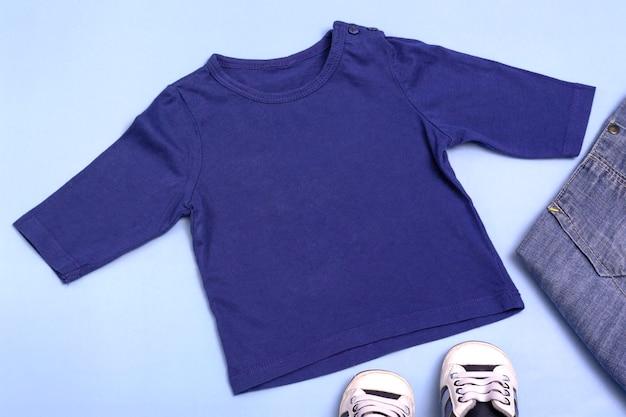 Maqueta para diseño y colocación de logotipos, publicidad. raglán azul para niños, polo, vista superior de la blusa, maqueta sobre un fondo azul.