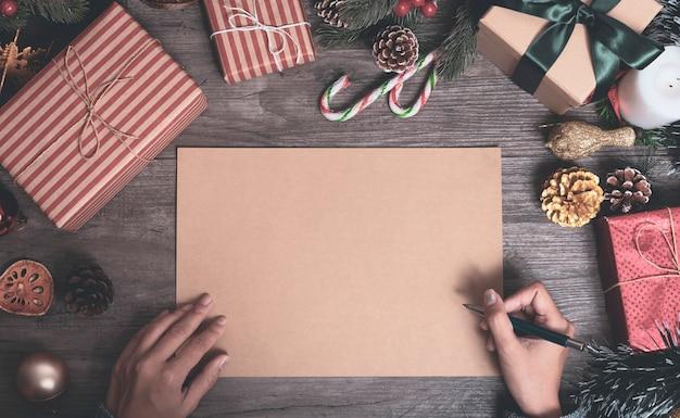 Maqueta del diseño del papel del saludo del día de fiesta de la navidad con la decoración en la tabla de madera.