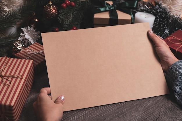 Maqueta de diseño de papel de saludo de vacaciones de navidad con decoración en mesa de madera.