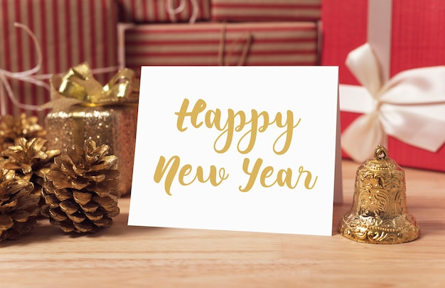 Maqueta del diseño de tarjeta de papel del saludo del día de fiesta de la feliz año nuevo con la decoración en la tabla de madera.
