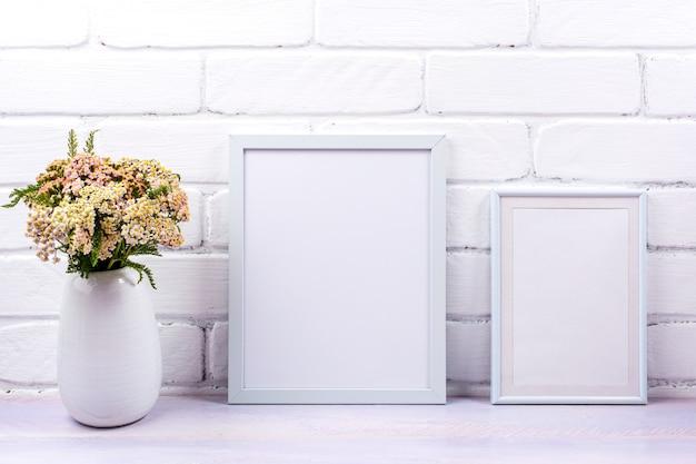 Maqueta de dos marcos blancos con flores silvestres de milenrama rosa en el jarrón