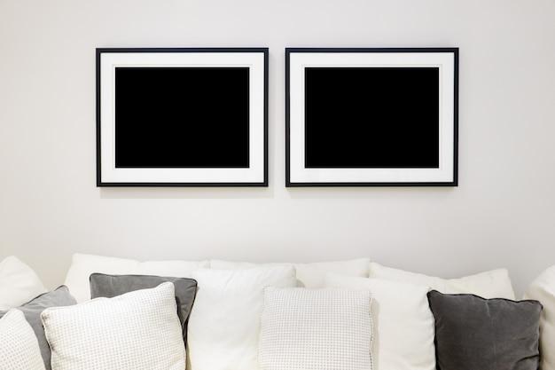 Maqueta de dos marcos de fotos para diseño de póster en pared blanca con sofá