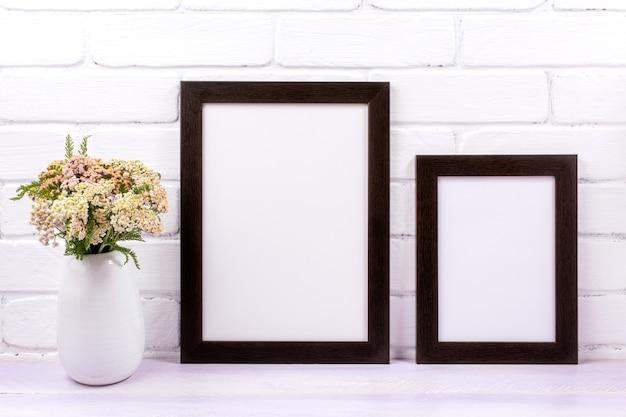 Maqueta de dos marcos marrones negros con flores silvestres de milenrama rosa en el jarrón